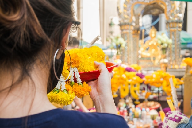 Woman make ceremonial offerings from floral garlands at the erawan shrine in bangkok, thailand