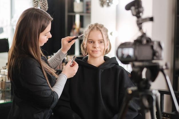 Женщина делает макияж для привлекательной женщины светлых волос в студии. видео нанесения визажиста