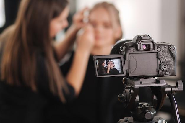 Женщина делает макияж для привлекательной женщины светлых волос в студии.