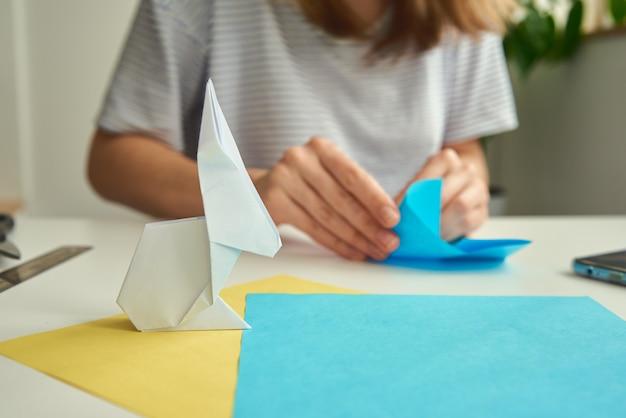 여자 색 종이에서 종이 접기 부활절 토끼 만들기