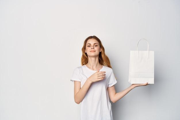 女性は手でエンターテインメントショッピングのパッケージでtシャツを作ります。高品質の写真