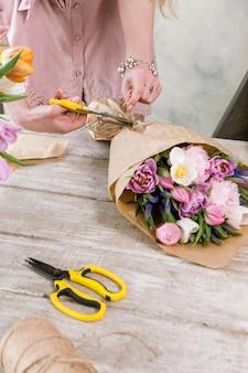 여자는 꽃 가게에서 튤립 꽃다발을 만듭니다. 젊은 꽃집은 축제 플로리스트가 나무 배경에 워크샵에서 조립하도록