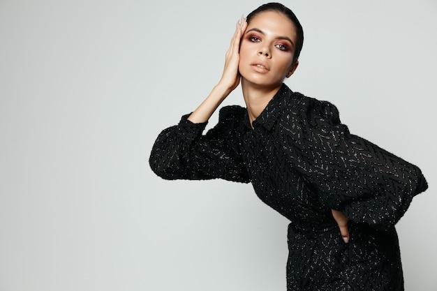 Женщина макияж сердце в черном модном платье крупным планом