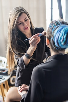 ビューティーサロンでフェイスユースブラシにスキントーンファンデーションパウダーブラッシュを塗る女性メイクマスター