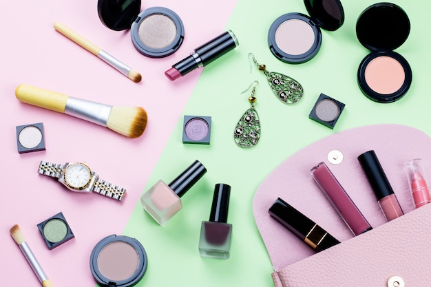 Woman make up products and accessories on pastel table