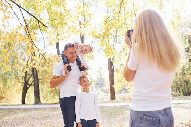 여자는 가을 공원에서 아이 들과 함께 그녀의 남편의 사진을 만든다.