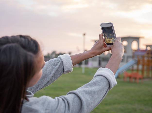 여자는 그녀의 휴대 전화에 일몰 하늘 사진을 만든다.