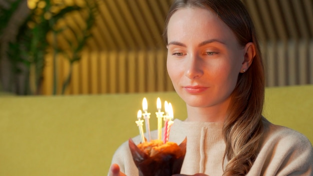 Женщина загадывает желание, задувает свечи на именинном торте и смеется