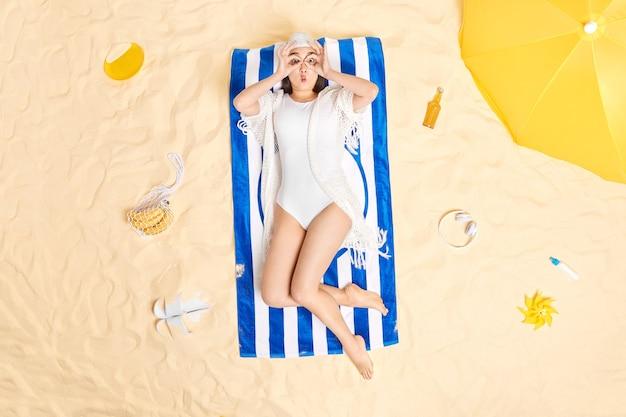 女性は目の上で双眼鏡を作り、スイムハットを着用し、白いビキニはさまざまなアイテムに囲まれた青い縞模様のタオルでビーチポーズで日焼けします