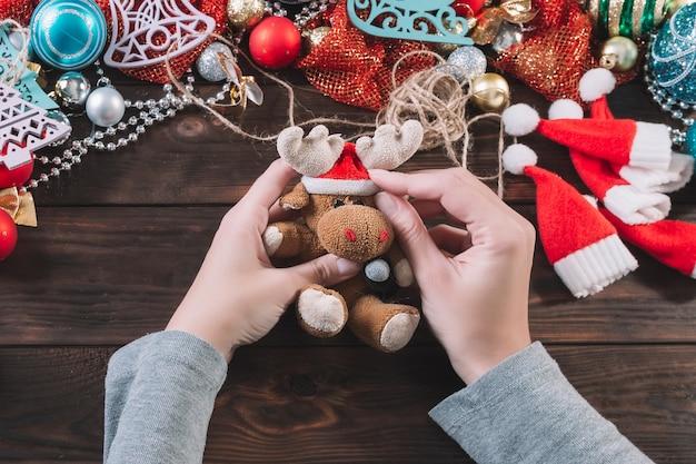 女性は暗い木製のテーブルでクリスマスプレゼントを作ります。
