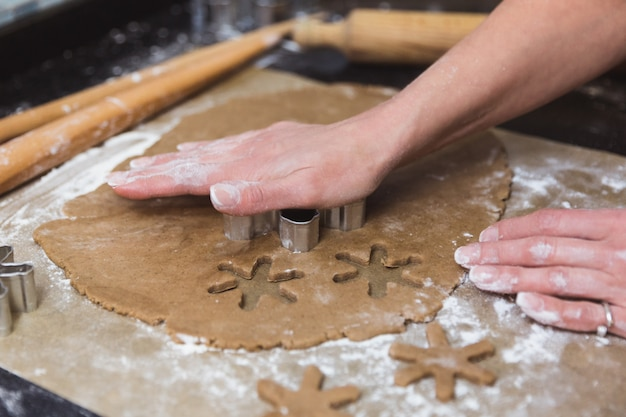 Woman makes christmas gingerbread cookies on black and red