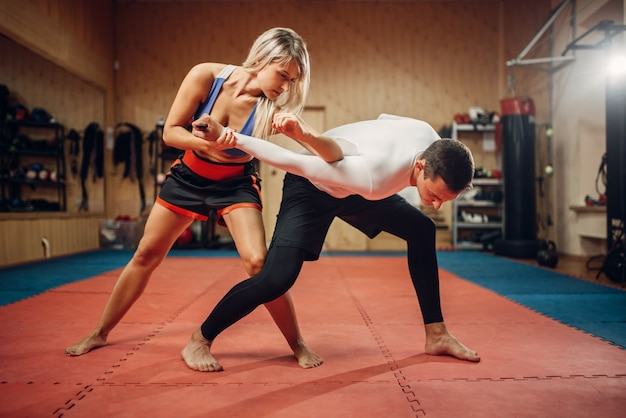 Woman makes elbow kick, self-defense workout with male personal trainer, gym interior. female person on training, self defense practice