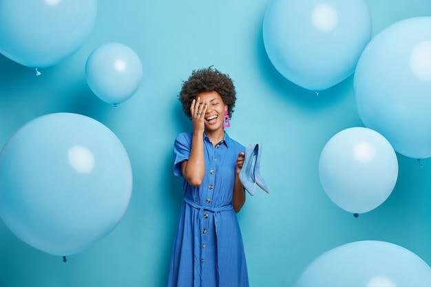 여자는 얼굴 손바닥 미소를 광범위하게 보유하고 하이힐 신발을 착용하고 파란색에 세련된 드레스 포즈를 취합니다.