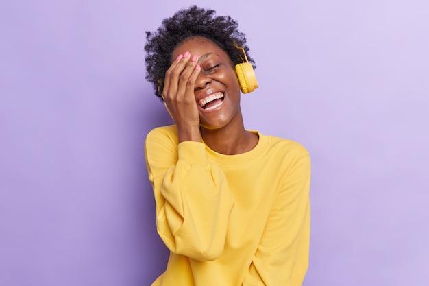 女性は顔の手のひらを笑顔にします非常に面白いものを広く笑います紫色に分離された黄色のジャンパーに身を包んだヘッドフォンを介して音楽を聴きます