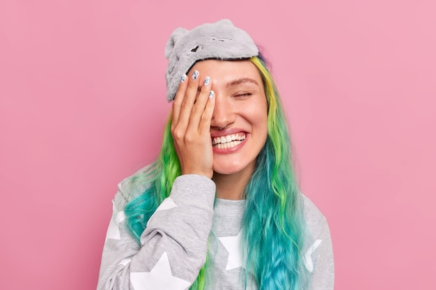 Woman makes face palm smiles gladfully hears positive news enjoys good morning dressed in slumber suit has trendy colored hair poses on pink