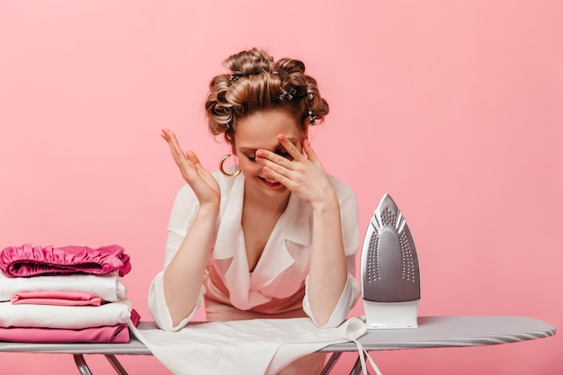 Woman makes facepalm, leans on ironing board on pink wall