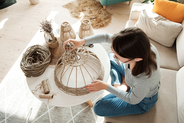 여자는 집에서 황마 밧줄로 수제 diy 램프를 만듭니다.