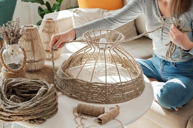 집에서 황마 밧줄로 수제 diy 램프를 만드는 여자