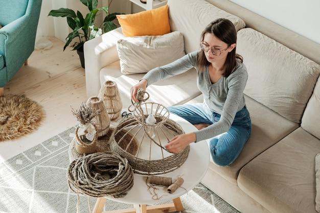 황마 밧줄로 수제 diy 램프를 만드는 여자
