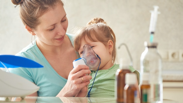 Woman makes inhalation to a child at home. brings the nebulizer mask to his face. inhales the vapor of the medication. the girl breathes through the mask. medicine on the table.