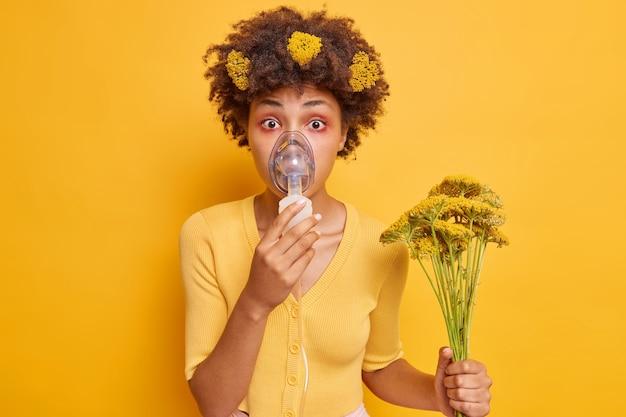 女性は吸入ネブライザーを着用します酸素マスクを着用しますアレルギーのために呼吸が困難です野生の花の花束を保持します黄色のジャンパーを着用します屋内でポーズをとる