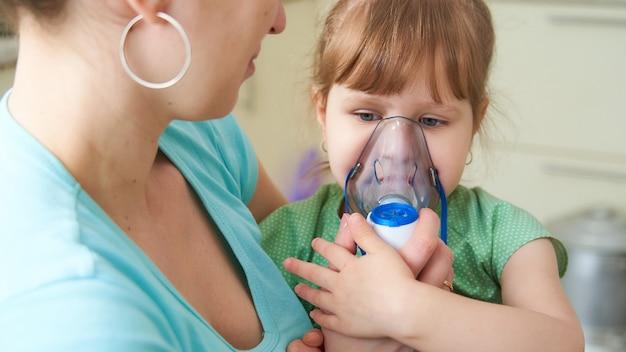 Женщина делает ингаляцию ребенку дома. подносит маску к небулайзеру. вдыхает пары лекарств. девушка дышит через маску. лекарство на столе.