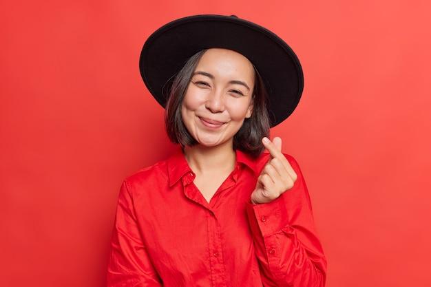 女性は韓国人をサインのように笑顔にし、愛を優しく表現します。鮮やかな赤に黒い帽子とシャツのポーズを着ています。
