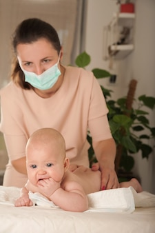 A woman makes a massage to a newborn in a medical mask.