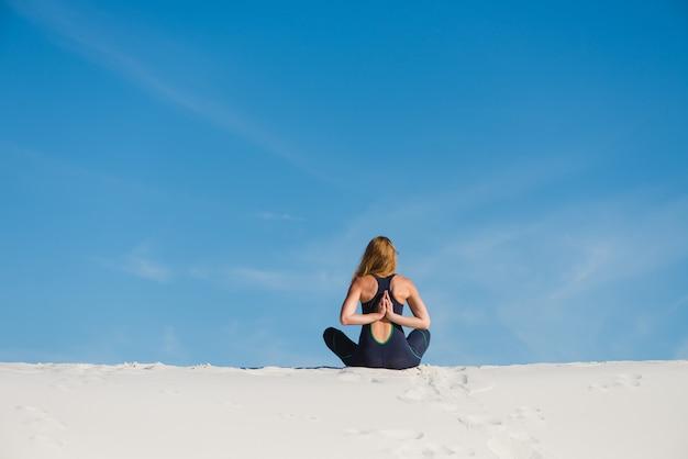 Женщина делает медитацию и намасте со спины