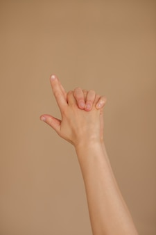 Woman makes mudra on beige background. yoga and meditation.