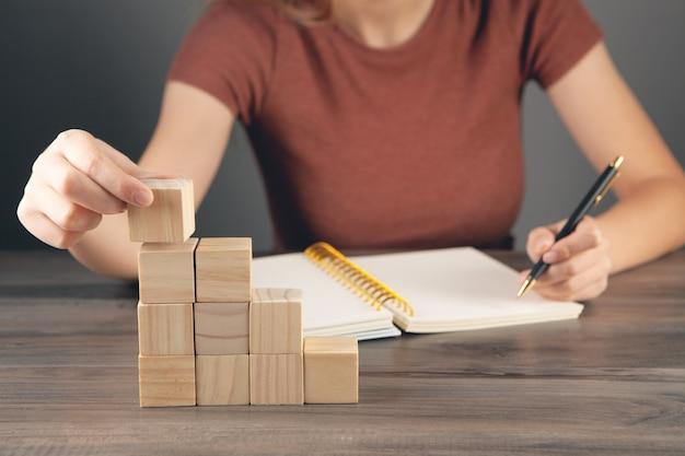 여자는 공책에 메모를 하고 큐브 사다리를 들고 있다