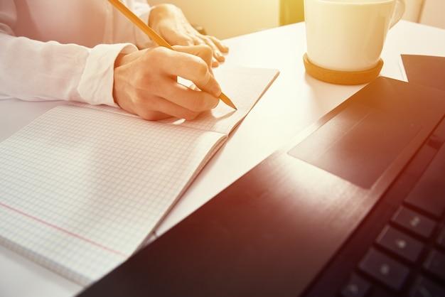 Женщина делает заметки в блокноте и использует ноутбук для учебы