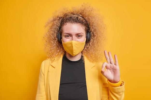Женщина делает нормальный жест говорит, что все под контролем, носит защитную маску от коронавируса, слушает музыку в наушниках