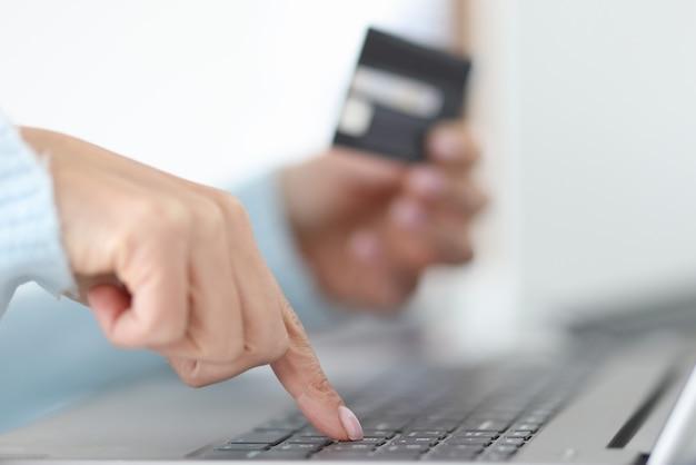 女性は銀行カードの概念によるラップトップオンライン支払いを介してオンライン支払いを行います