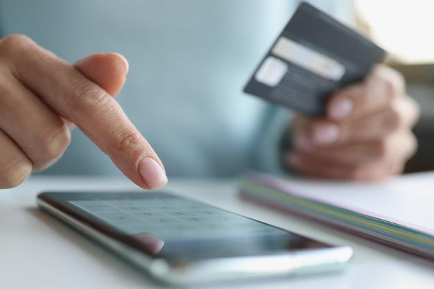女性は銀行カードの概念によるスマートフォンのオンライン支払いを介してオンライン支払いを行います