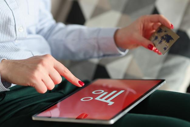 女性はタブレットでオンライン購入を行い、銀行カードを持っています。オンラインショッピングのコンセプト