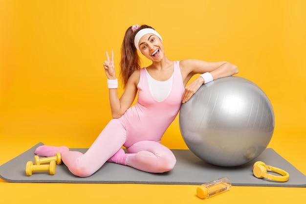 Женщина делает жест мира, одетая в активную одежду, опирается на надутый мяч для фитнеса, позирует на поездах karemat с гантелями, использует наушники для прослушивания музыки. аэробика