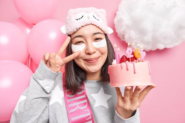 Woman makes peace gesture on eye smiles pleasantly has joyful mood holds tasty cake celebrates birthday