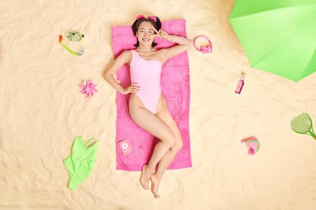 女性はビキニを着た目に平和のジェスチャーをしますタオルの上に横たわるビーチで夏休みを過ごす屋外で日光浴のポーズを楽しんでいます。