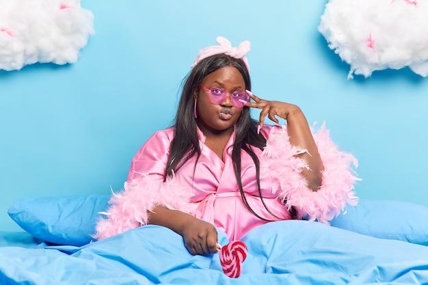 女性は目に平和のジェスチャーをする長い爪を持ち、唇を折りたたんだまま、おいしいキャンディーを青に隔離された柔らかい羽毛布団の下でベッドに留める