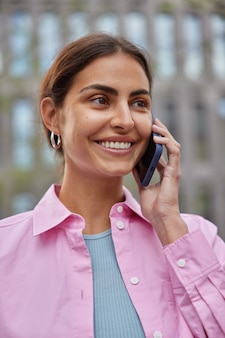 여자는 현대적인 스마트폰 미소를 사용하여 전화를 걸고 기분 좋게 분홍색 셔츠를 입고 거리에서 포즈를 취합니다. 사람들이 기술 라이프 스타일 개념입니다.
