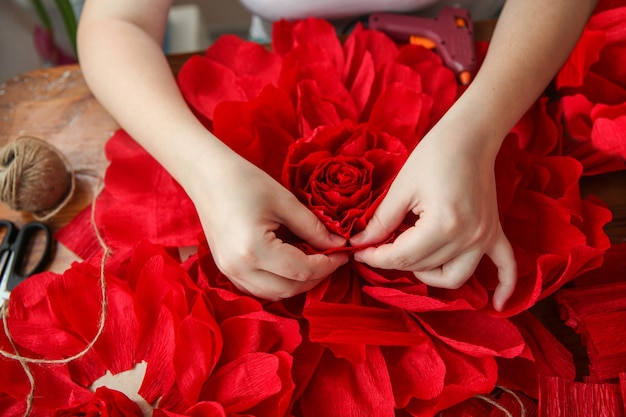 A woman makes red paper flowers. only the hands are in the frame. top view. high quality photo