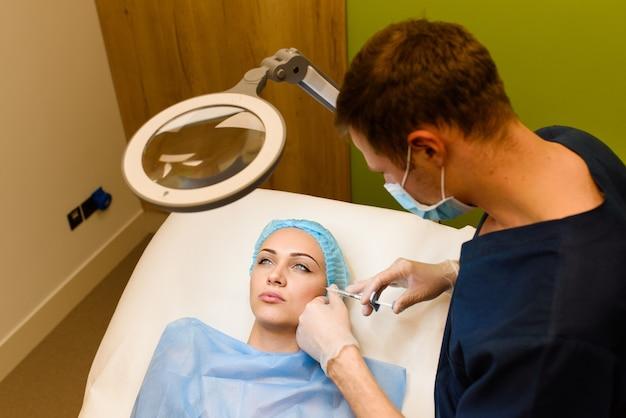 Женщина делает омолаживающие инъекции для лица для увеличения губ