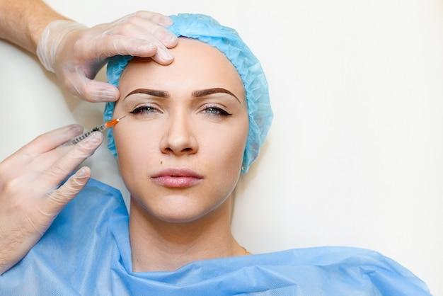 여성이 눈 구석의 주름을 조이고 부드럽게하기 위해 활력을주는 얼굴 주사 절차를 만듭니다.