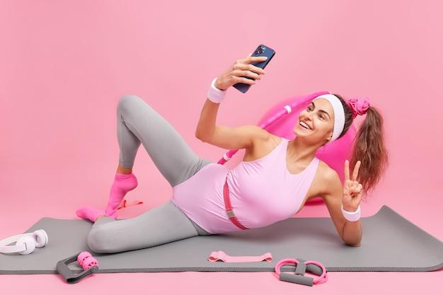 Женщина делает селфи держит мобильный телефон перед лицом делает жест мира имеет темные волосы, связанные в хвостик, одетая в боди, лежит на коврике для фитнеса со спортивным оборудованием вокруг