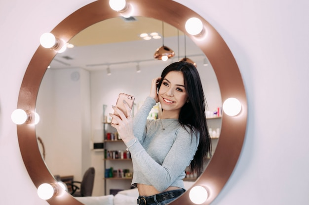 Woman makes selfie in makeup mirror with lamps