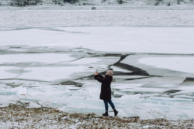 A woman makes a selfie on the phone in the winter on the shore of frozen river with ice floes.
