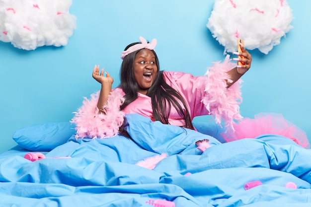 Woman makes selfie portrait with modern smartphone wears headband dressing gown has fun in bed at home laughs happily isolated on blue