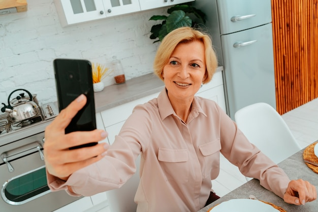 Woman makes a selfie with a smartphone during the breakfast