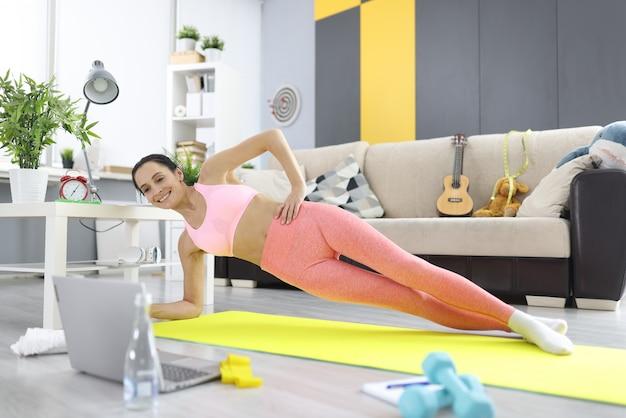 女性はサイドプランクを作り、ラップトップモニターを調べます。自宅でのオンラインフィットネストレーニングのコンセプト